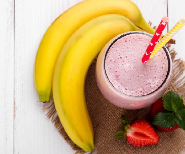 Strawberry smoothie with oatmeal and banana on white wooden table